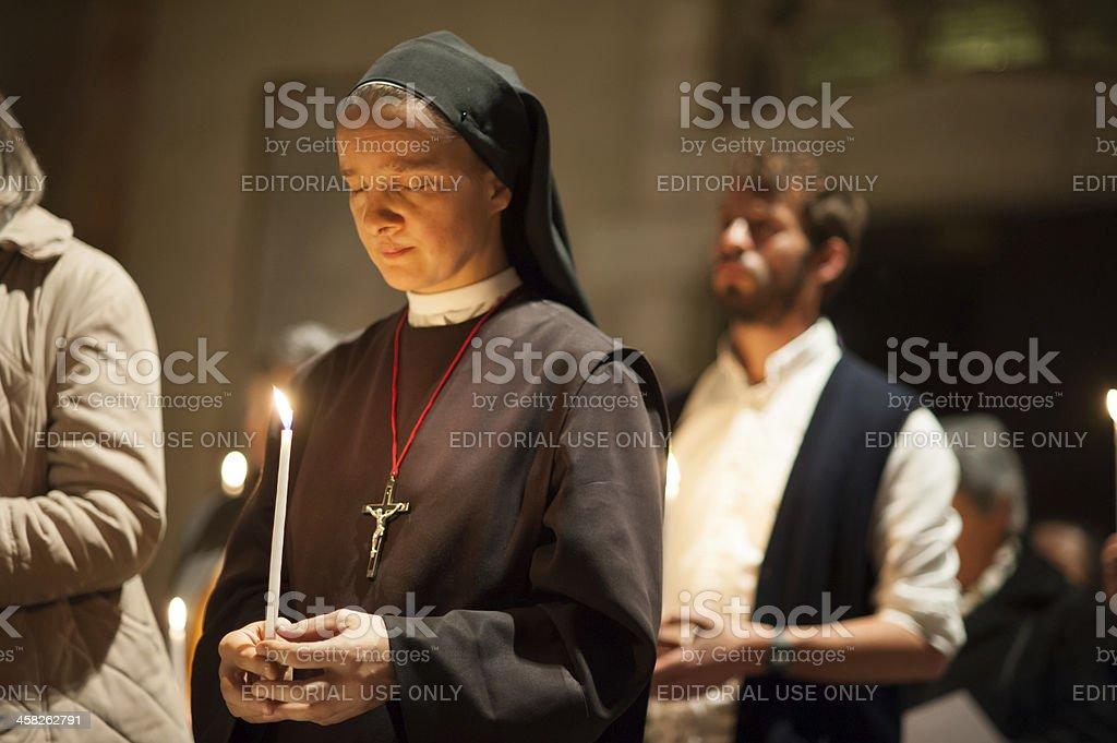 Catholic nun praying with candle stock photo