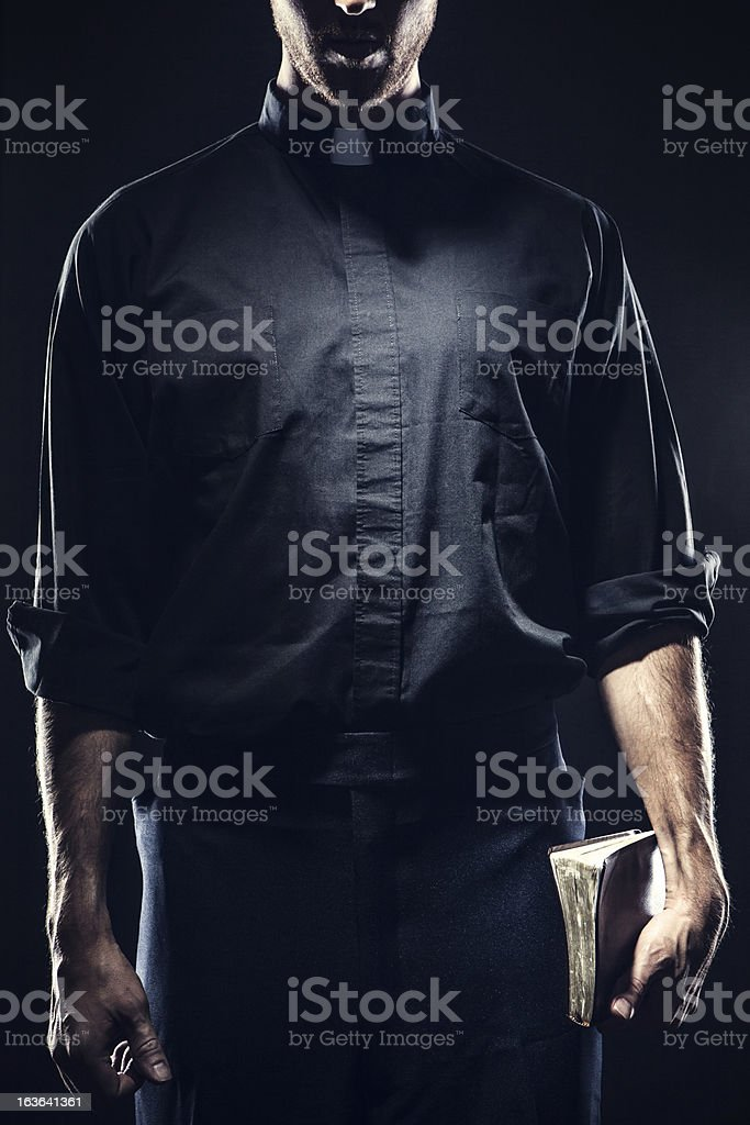 Catholic Priest Holding a Bible stock photo