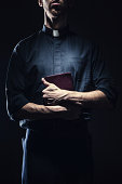 Catholic Priest Holding a Bible