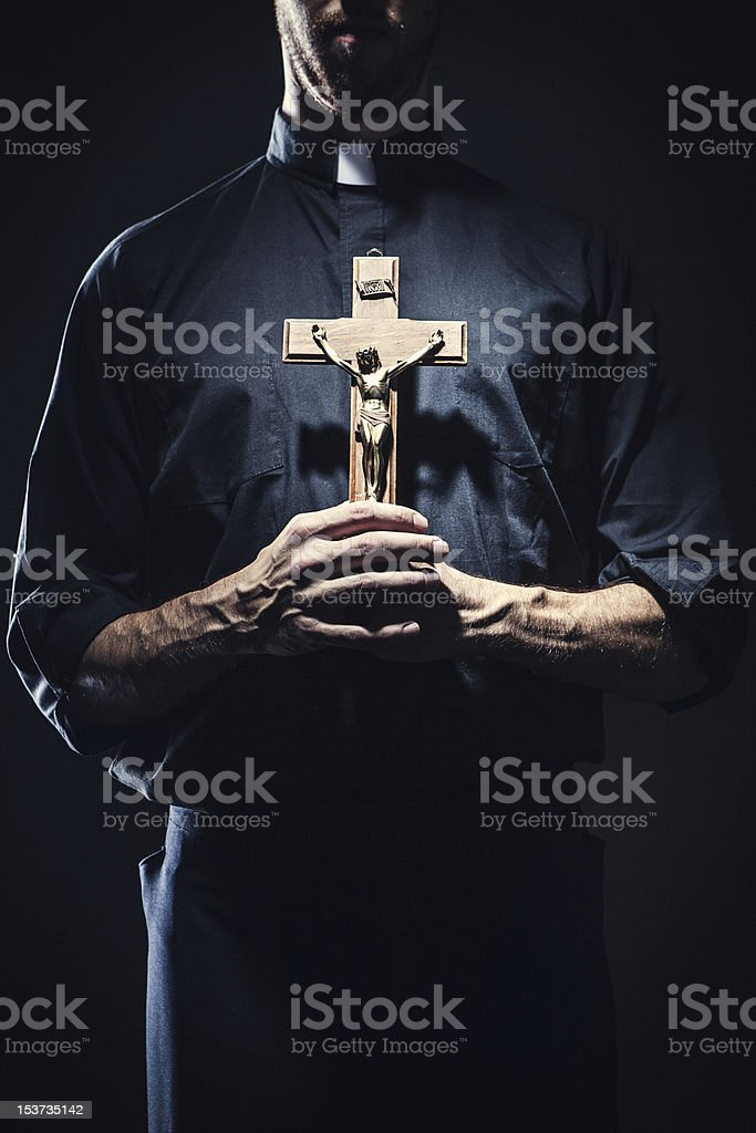 Catholic Priest Holding a Wooden Crucifix stock photo