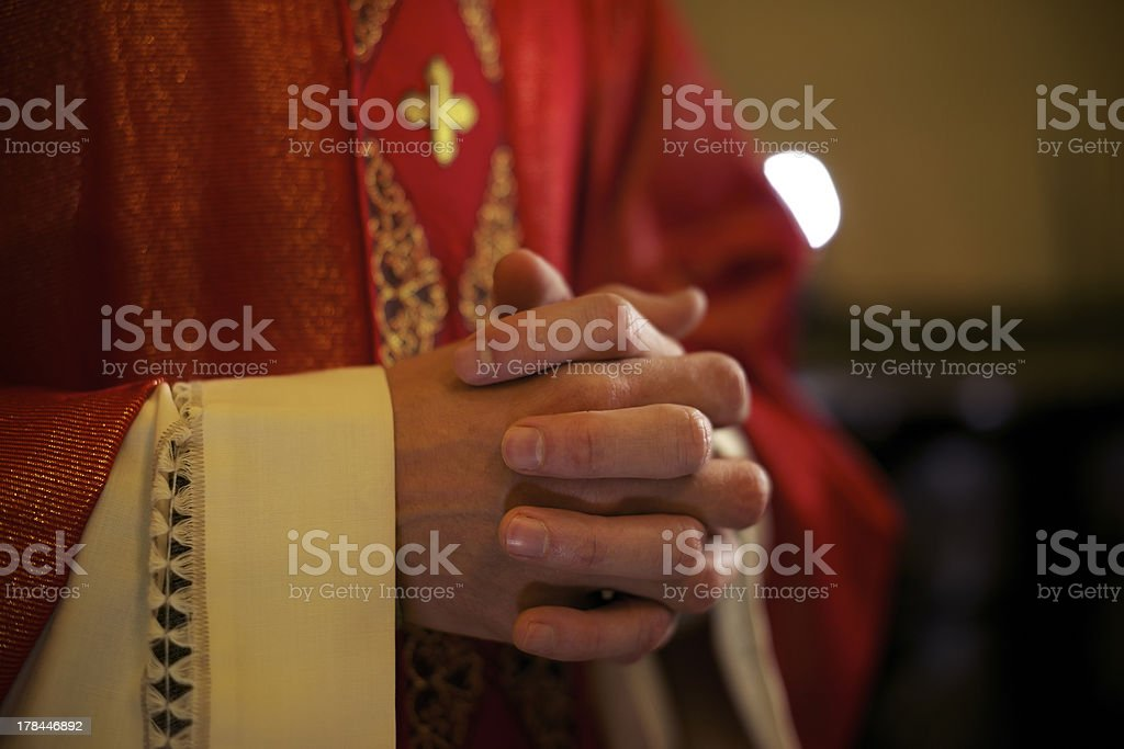 Catholic priest on altar praying during mass stock photo