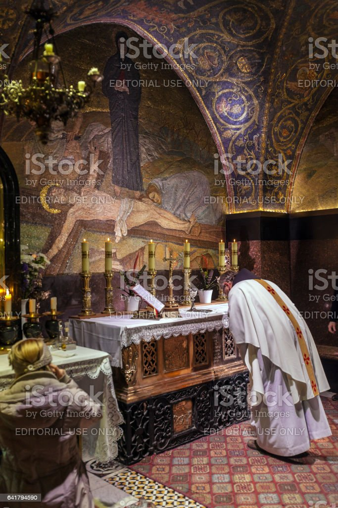 JERUSALEM, ISRAEL - FEBRUARY 22, 2013: Catholic priest praying  in Temple of the Holy Sepulchre stock photo