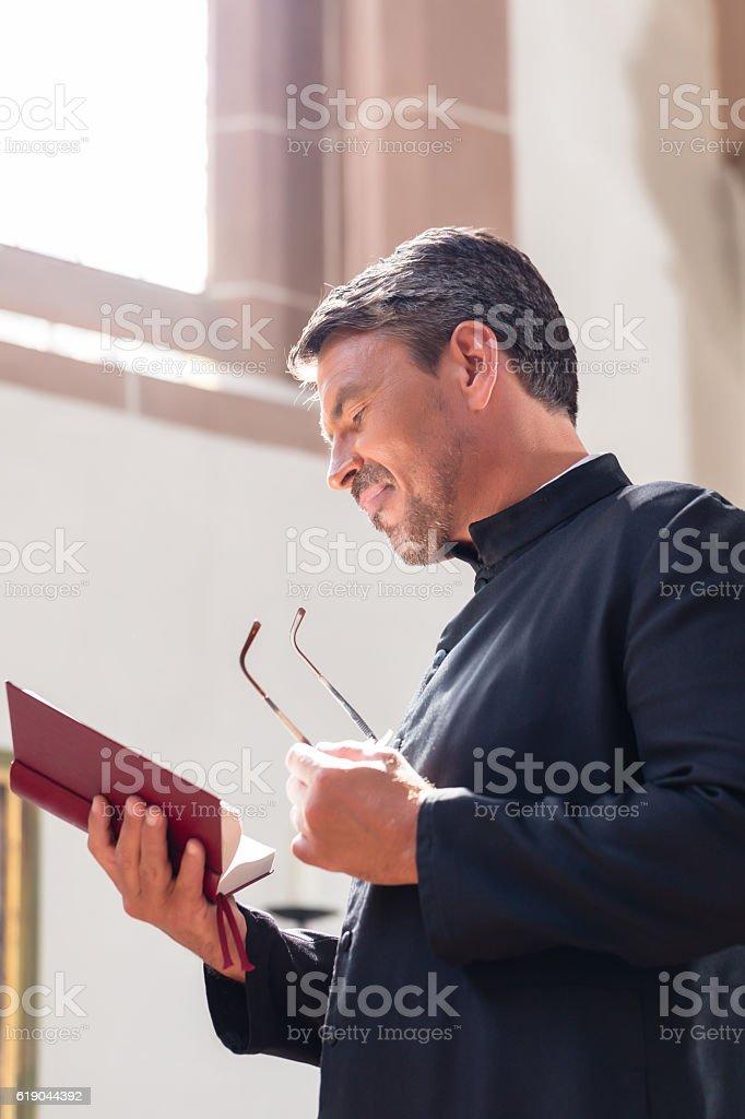 Catholic priest reading bible in church stock photo