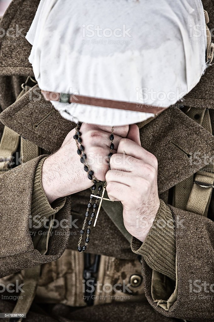 WWII US Catholic Soldier Praying On His Rosary Beads stock photo
