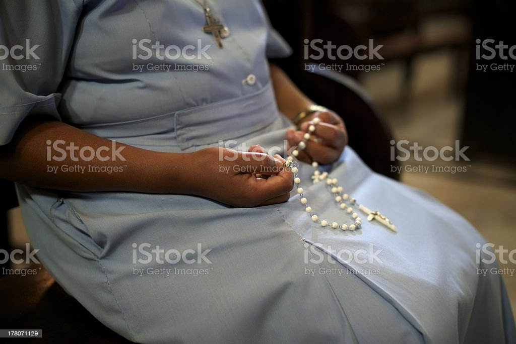 A Catholic woman holding beads in church stock photo