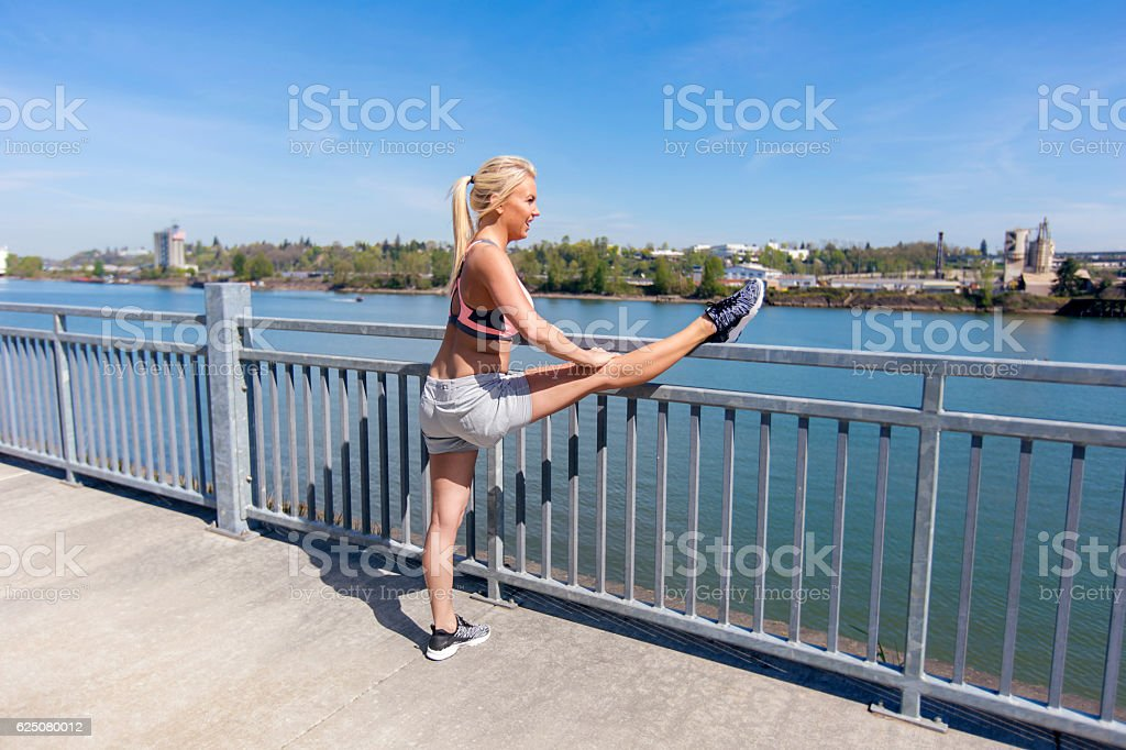 Caucasian adult female stretching her leg along a metal rail stock photo