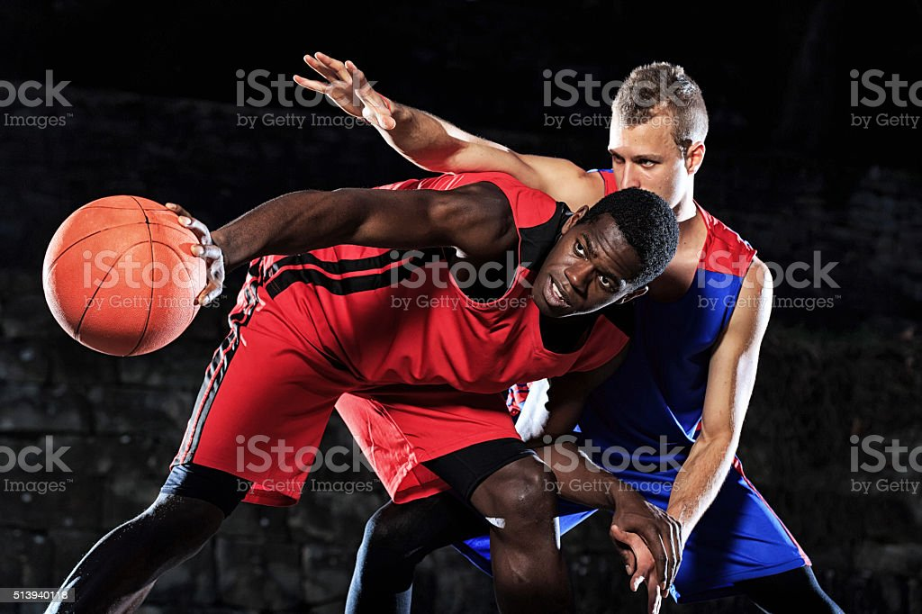 Caucasian and african basketball players in defence on black background stock photo