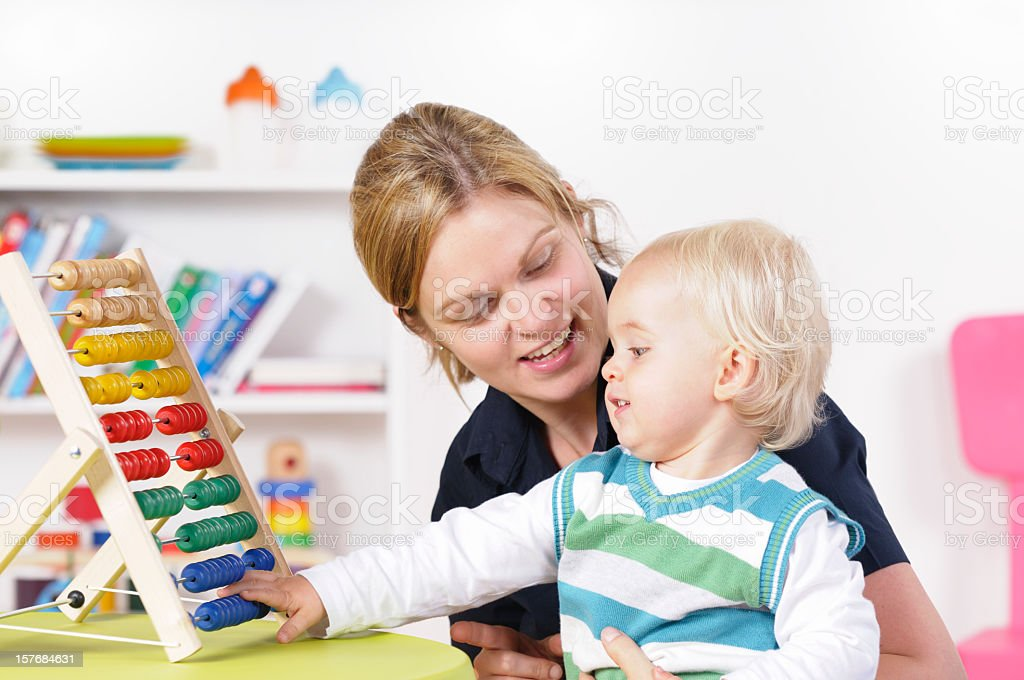 Caucasian Baby Boy/ Toddler Playing While Being Surpervised stock photo