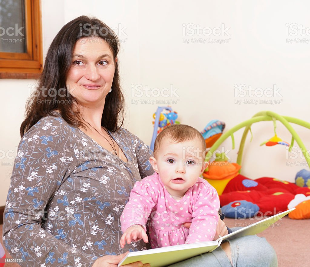 Caucasian Baby Girl And Carer At Storytime stock photo