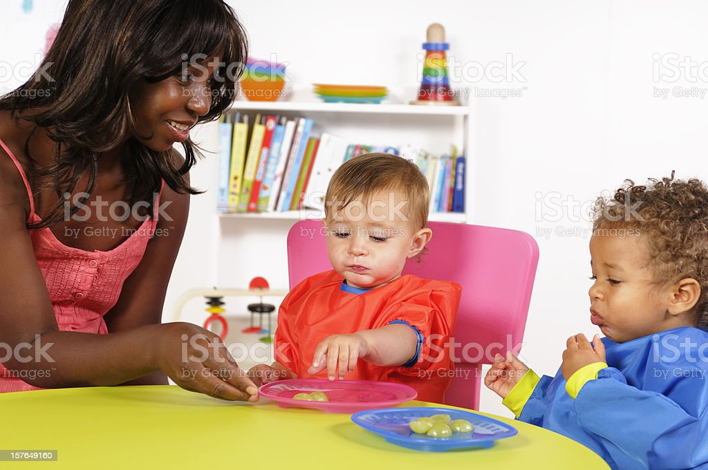 Caucasian Baby Girl And Her Peer Being Supervised While Eating stock photo