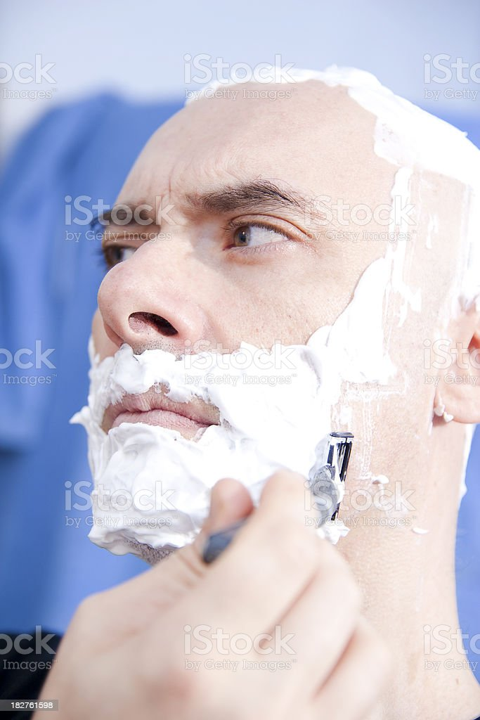 Caucasian bald man shaves in the bathroom royalty-free stock photo