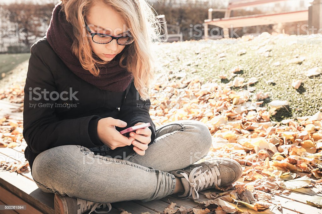 Caucasian blond teenage girl in jeans with mobile phone stock photo