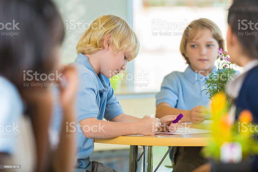 Caucasian blonde boys in private elementary school classroom stock photo