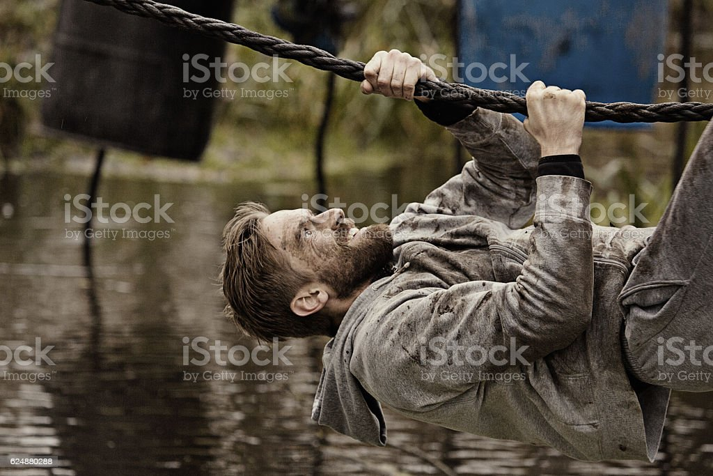 Caucasian blonde handsome man climbing obstacle during a mud run stock photo