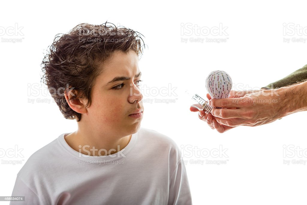 Caucasian boy puzzled by 3d and real lightbulbs stock photo