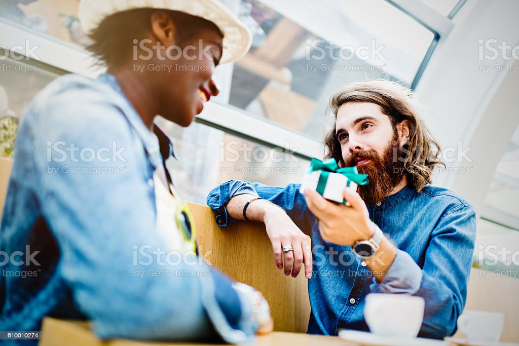 Caucasian boyfriend giving present to his African girlfriend stock photo