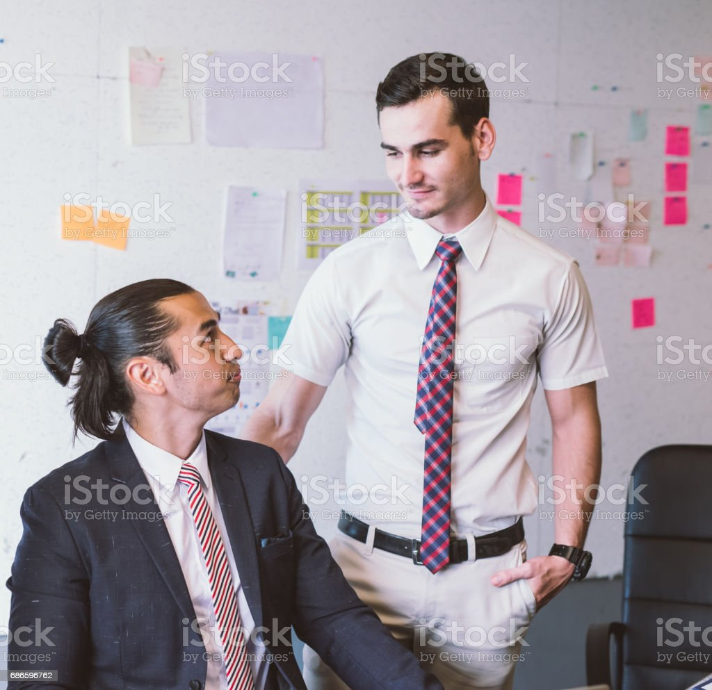 Caucasian business executive praising subordinate by giving a pat on the shoulder with eye contact. stock photo