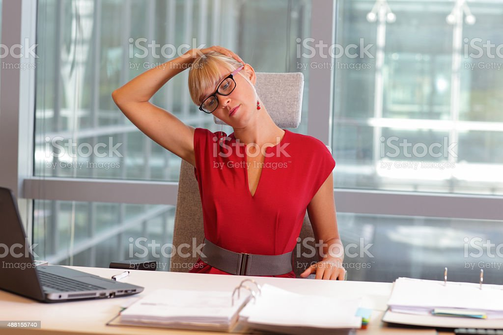 caucasian business woman in eyeglasses relaxing neck,stretching arm stock photo