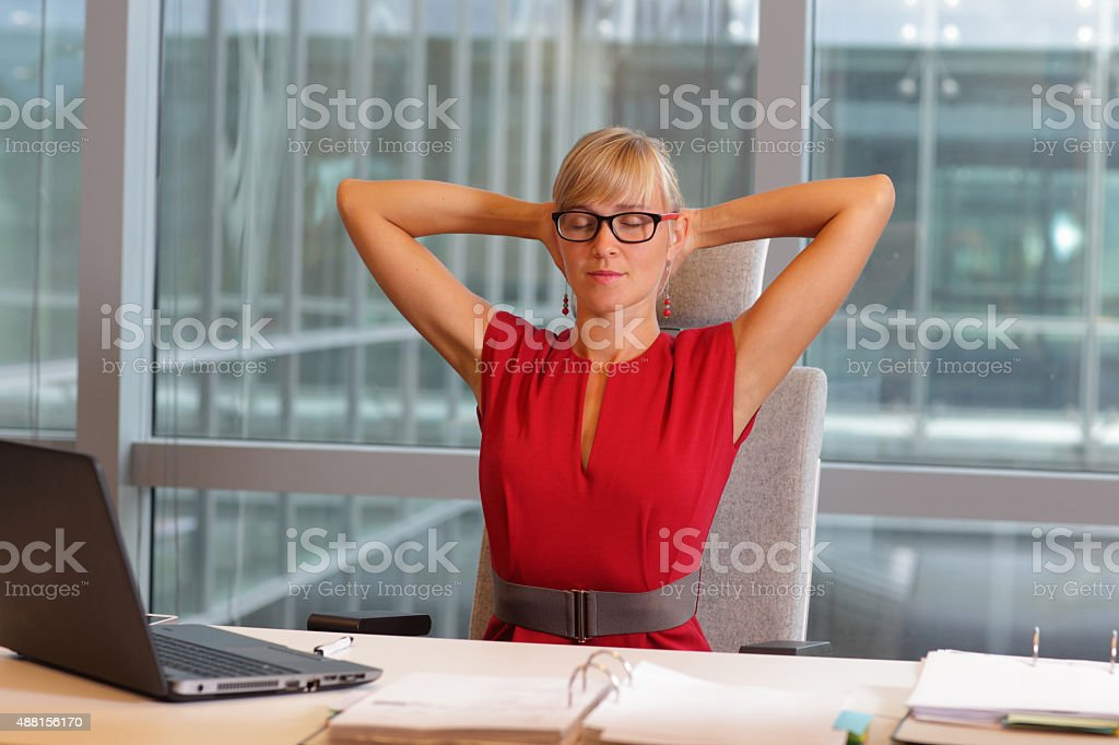 caucasian business woman in eyeglasses relaxing neck,stretching arms stock photo