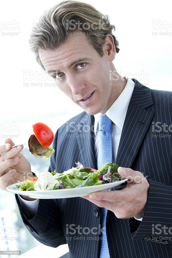 Caucasian Businessman eating salad in office stock photo