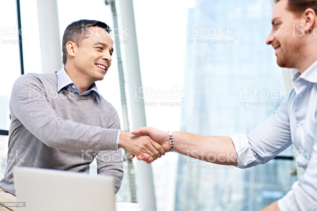 caucasian businesspeople shaking hands in office stock photo