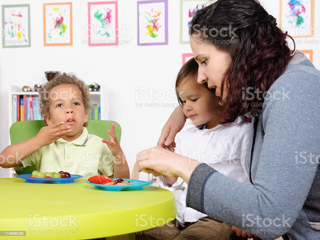 Caucasian Carer Assisting Toddler At Mealtime royalty-free stock photo