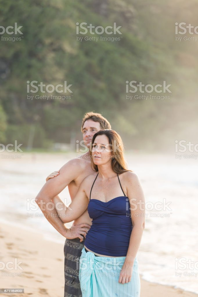 Caucasian couple embrace each other on a warm Hawaii beach stock photo