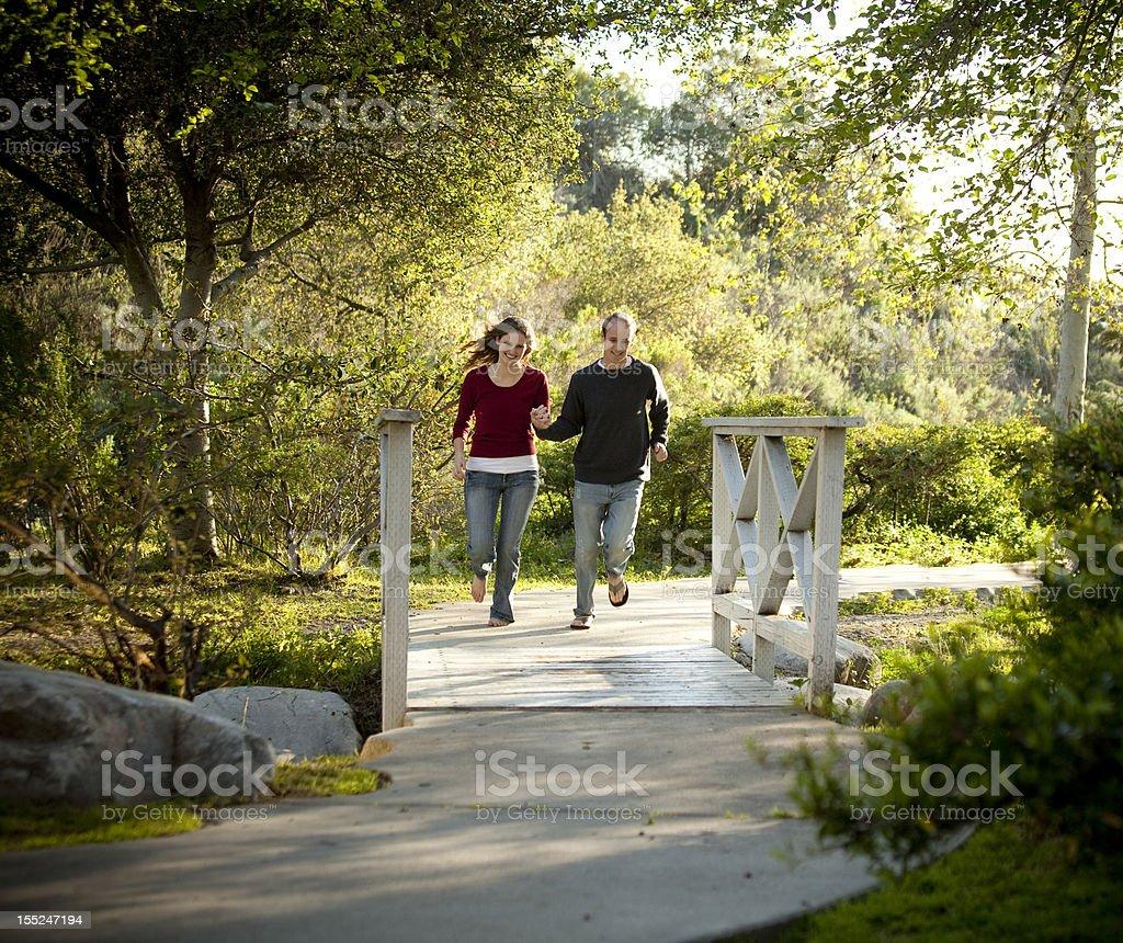 Caucasian couple running on outdoor wooden bridge royalty-free stock photo