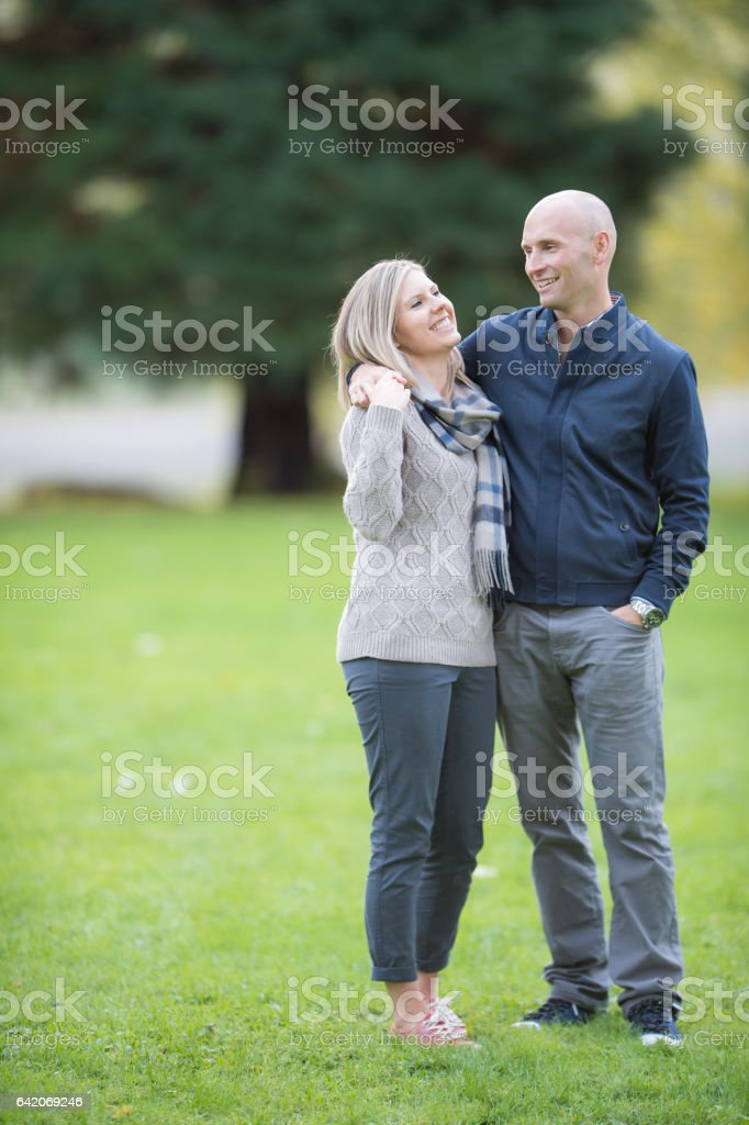 Caucasian couple taking a walk in the park stock photo