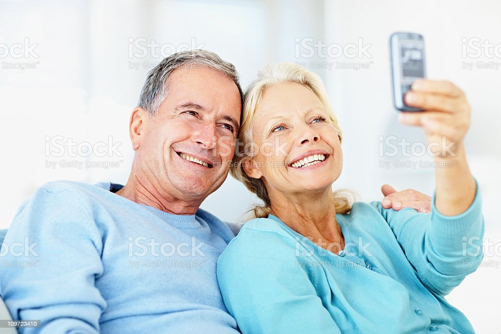 Caucasian couple taking picture of themselves royalty-free stock photo