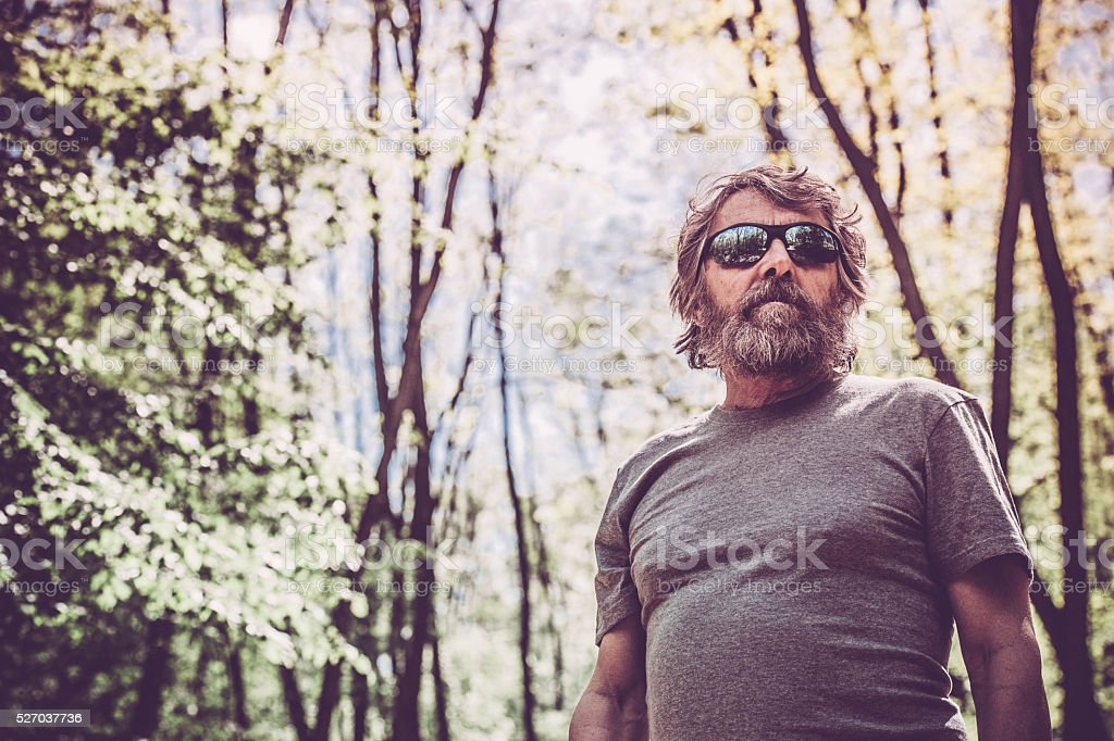 Caucasian elderly man with beard and sunglasses portrait in forest stock photo