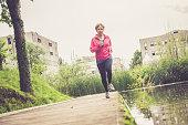 Caucasian elderly woman running in rainy  park Mediterranean Active Seniors