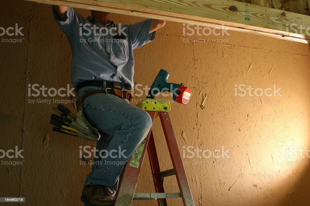 Caucasian Electrician on ladder wearing tool belt working In closet royalty-free stock photo