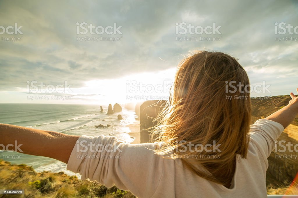 Caucasian female arms outstretched at sunset stock photo