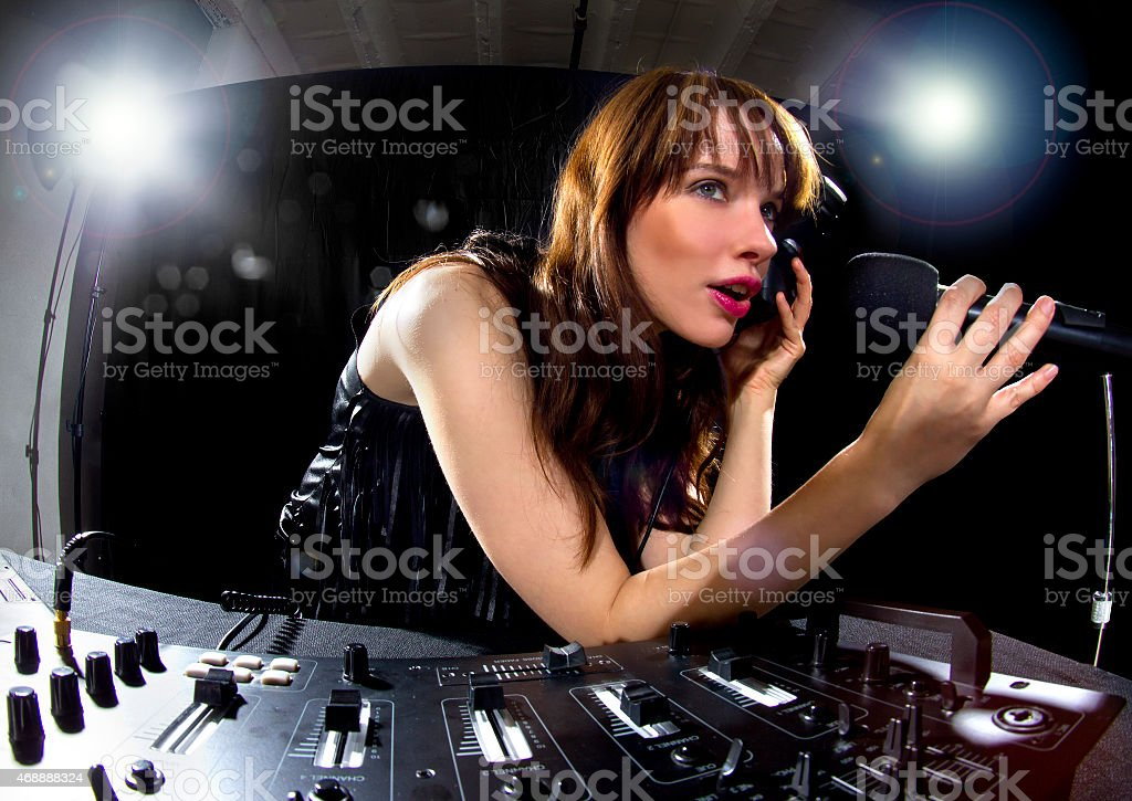 Caucasian Female DJ Speaking to a Microphone at a Nightclub stock photo