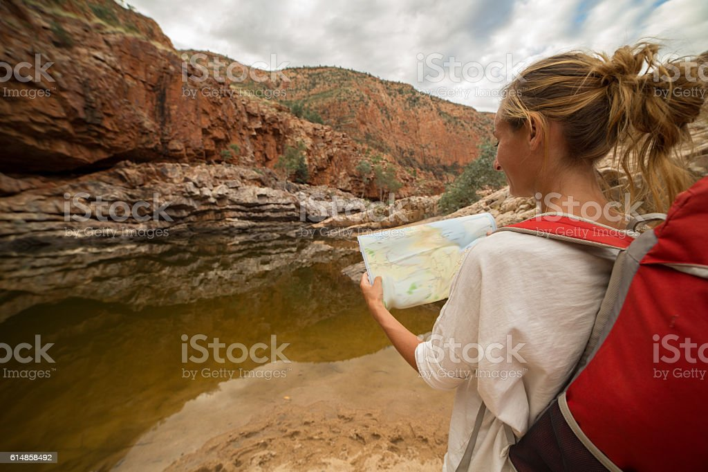Caucasian female hiking in the outback reads map for directions stock photo