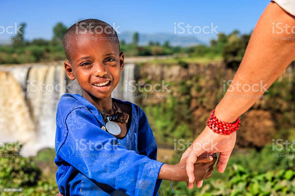 Caucasian female is holding young african child's hand stock photo