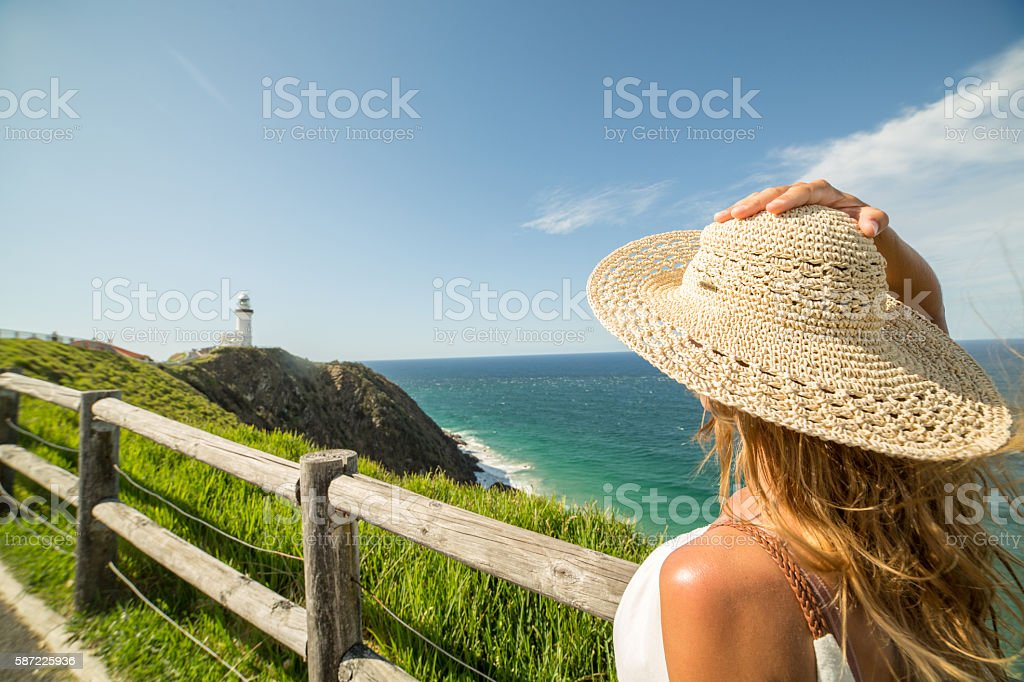 Caucasian female looks at seascape, wind blowing stock photo