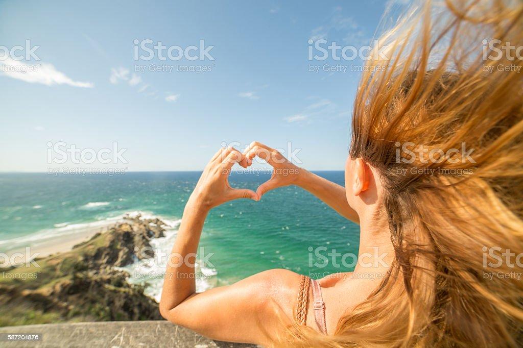 Caucasian female makes heart shape finger frame on seascape stock photo