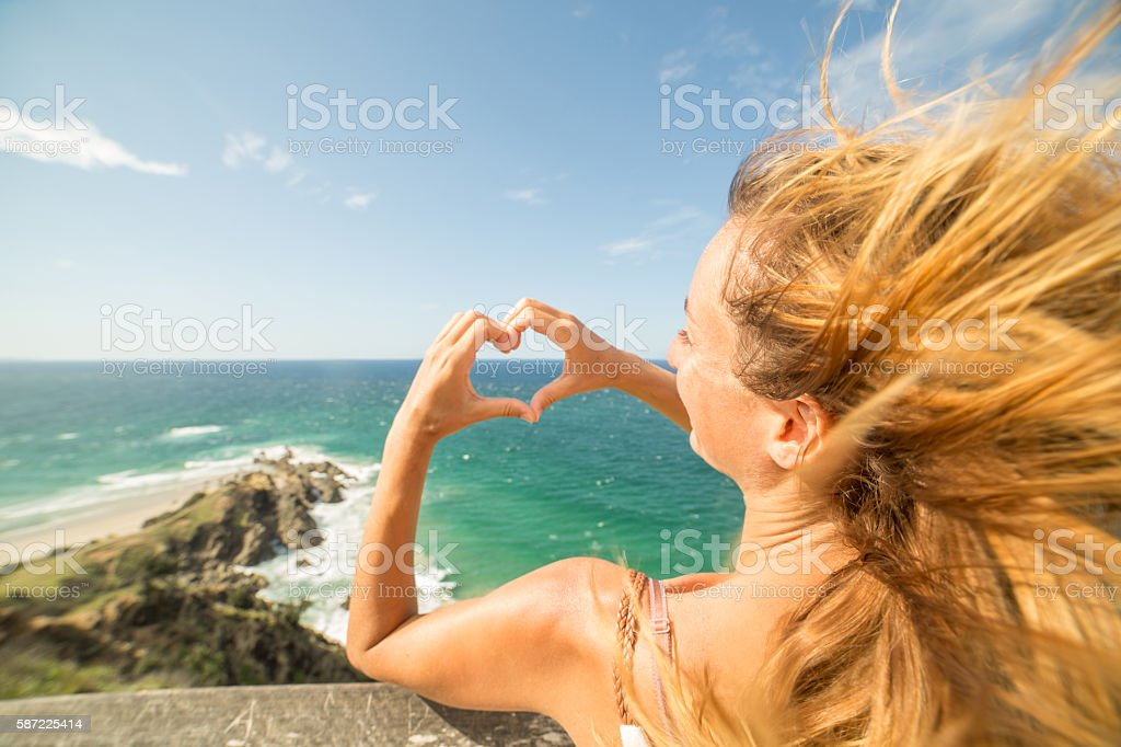Caucasian female makes heart shape finger frame on seascape stock photo