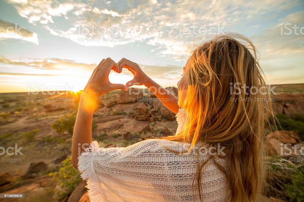 Caucasian female makes heart shape finger frame to spectacular landscape-sunrise stock photo