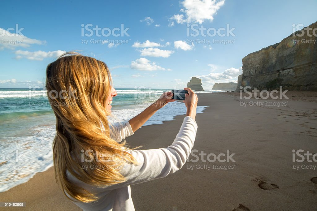 Caucasian female photographing sea rocks with mobile phone stock photo