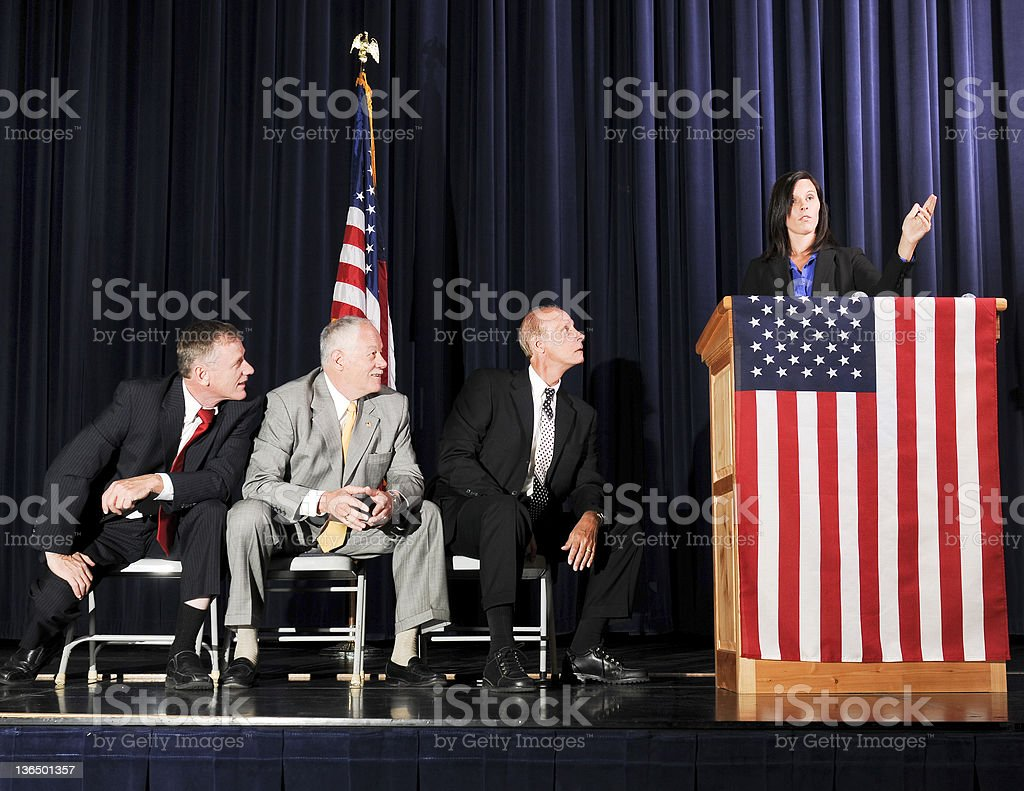 Caucasian Female Political Speaker with Very Attentive Male Listeners royalty-free stock photo
