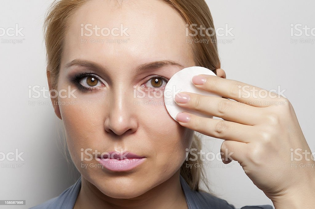 Caucasian female removing the make up from her face royalty-free stock photo