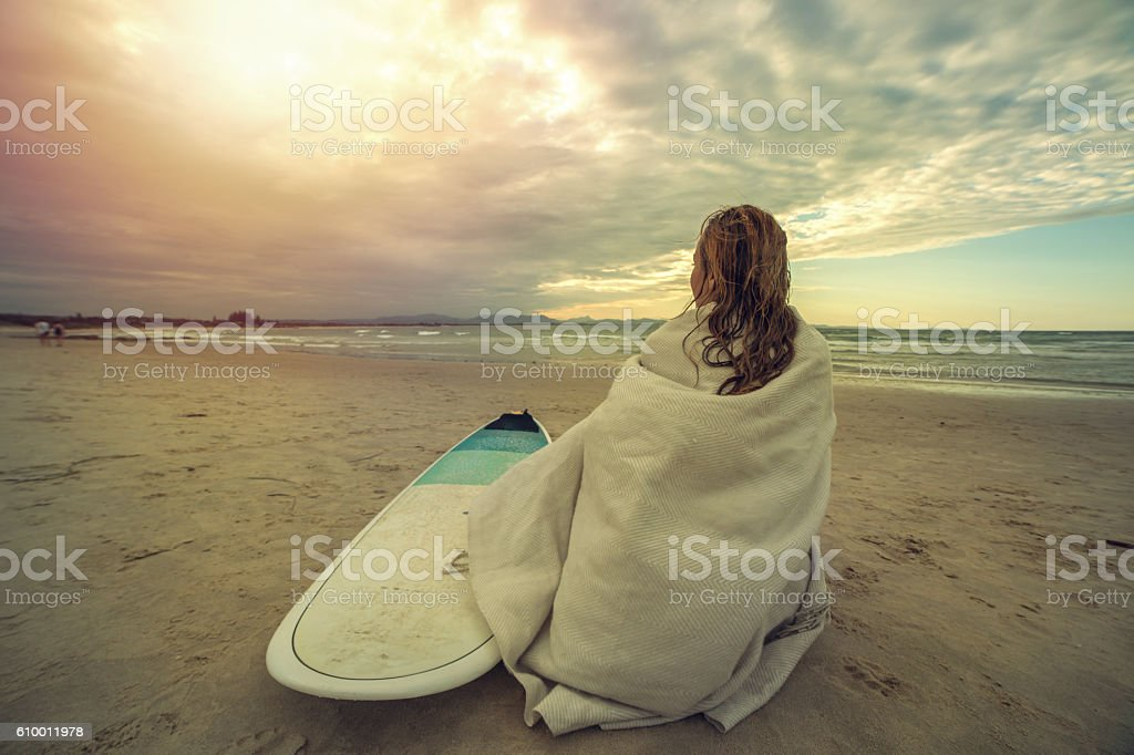 Caucasian female surfer sitting on the beach with the surfboard stock photo