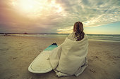 Caucasian female surfer sitting on the beach with the surfboard