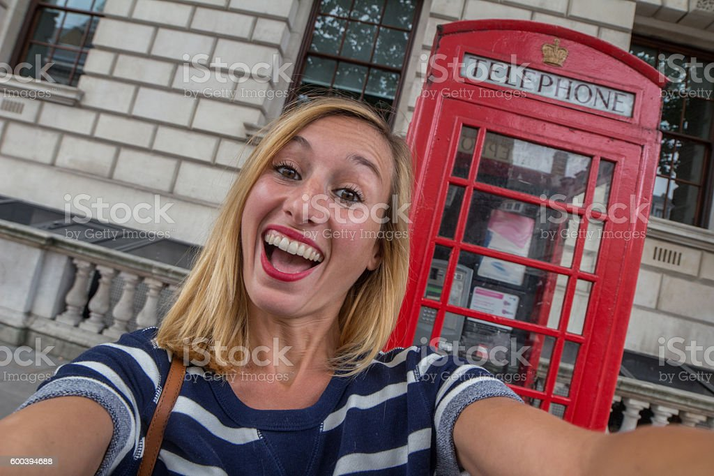 Caucasian female takes selfie with classic London phone booth stock photo