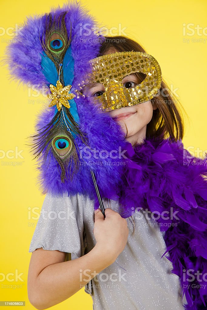 Caucasian girl 7-8, playing dress up feather boa and mask royalty-free stock photo