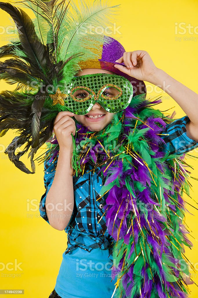 Caucasian girl 7-8, playing dress up feather boa, mask, hat stock photo