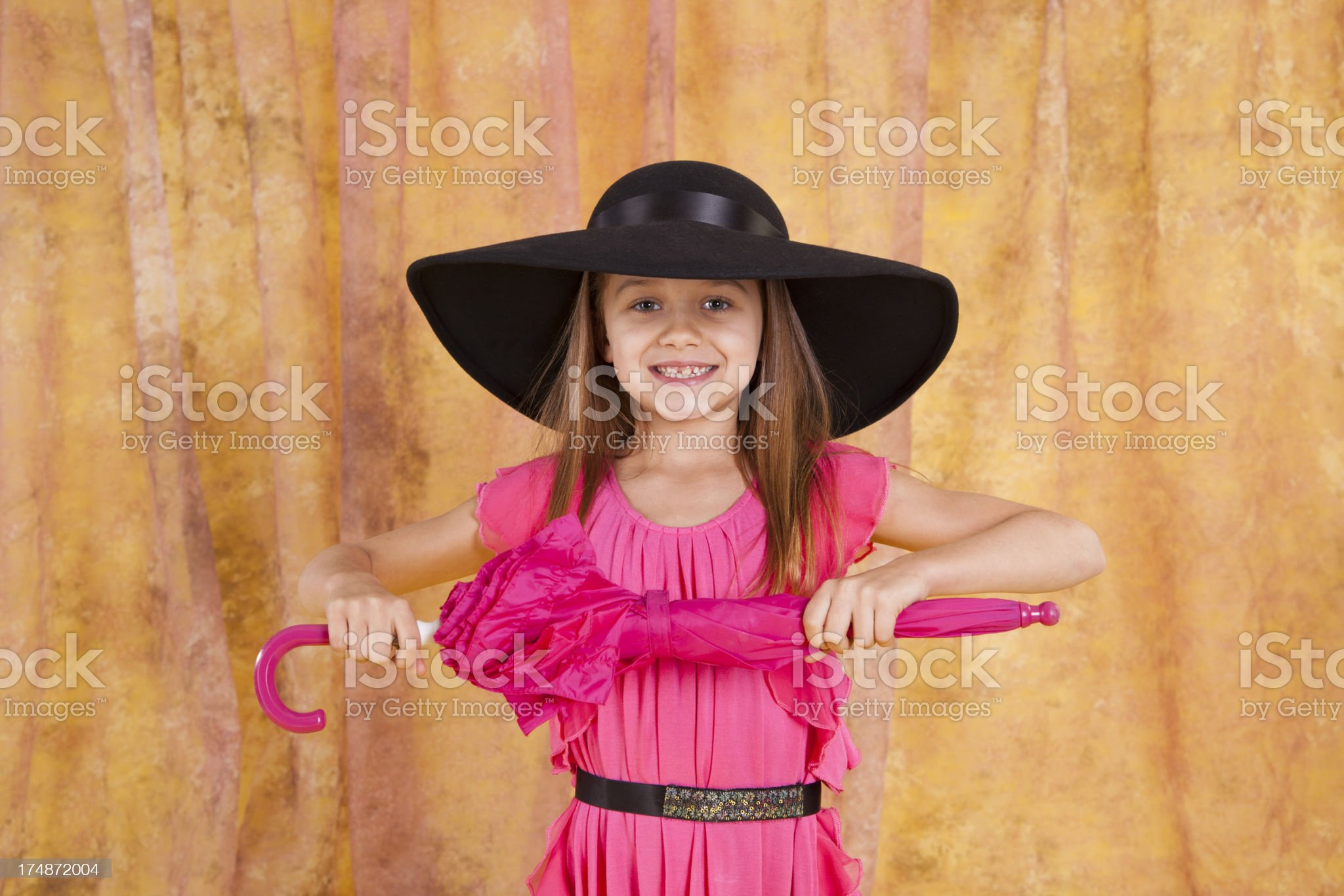 Caucasian girl 7-8, with umbrella wearing hat  looking at camera royalty-free stock photo